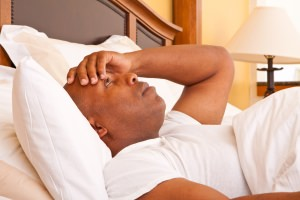 Man laying in bed unable to sleep