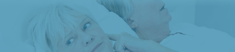 Elderly woman plugging her ears lying in bed