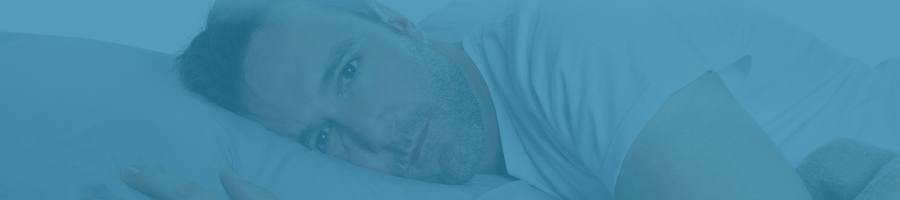 Man lying in bed having trouble sleeping
